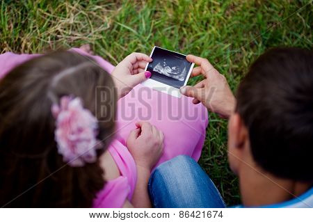 Prospective Parents Looking At Ultrasound Scan