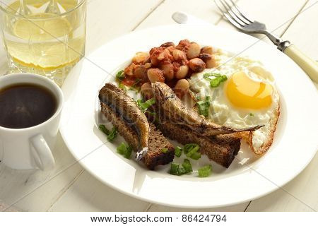 Breakfast with fried egg, beans, sprats