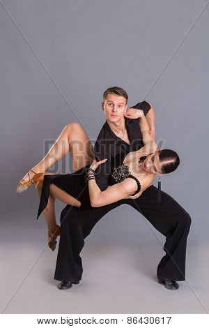 Ballroom dancing. Man and woman posing in dance pose on white