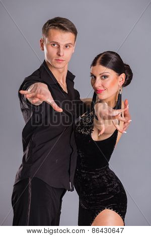 Man and woman posing in dance pose on white.
