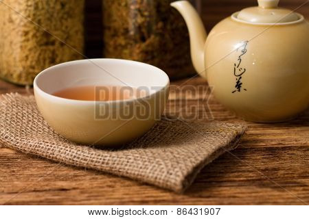 Chinese Tea In Cup With Kettle On Right