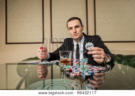 A man in a suit at the gaming table