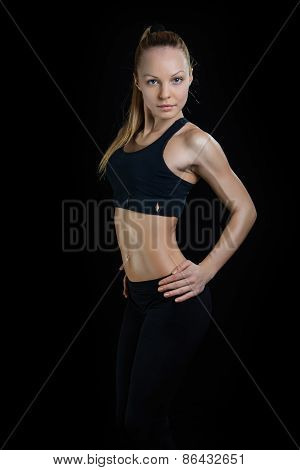 Athletic young woman showing trained beautiful body on a isolated black background