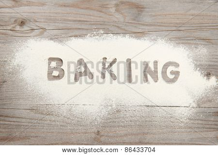 Word baking written in white flour on a old wooden table, low light vintage tone.