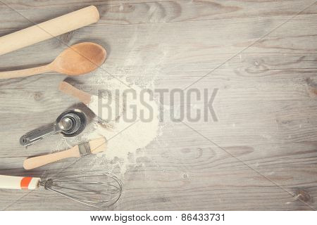 Baking utensils from top view on wooden table in vintage tone, copy space on side.