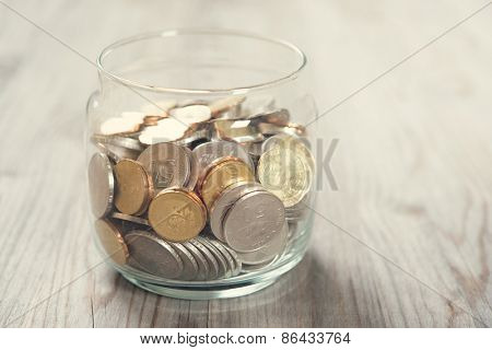 Coins in glass money jar, on wooden background.