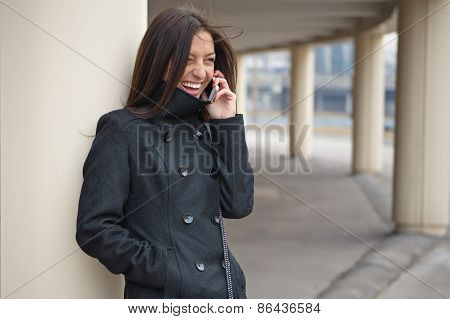 Young cheerful girl talking on the phone.