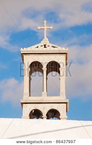Marble Bell Tower Of The Old Monastery On The Island Of Mykonos On The Background Of Sky. Greece.