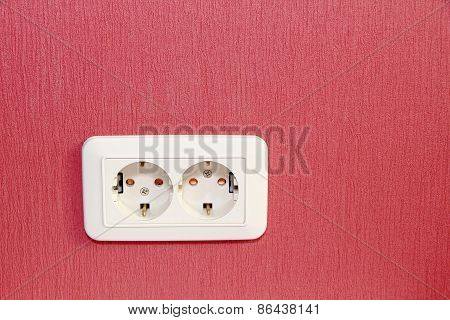 White Double Electrical Socket On Red Wall Empty Space.