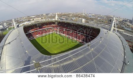 MOSCOW, RUSSIA - APR 28, 2014: People watch football match in Locomotive sports stadium at evening. Aerial view