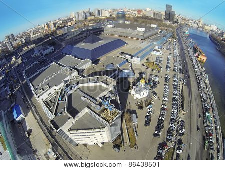 MOSCOW, RUSSIA - MAR 12, 2013: Church and car parking near Expo Center exhibition complex against cityscape at sunny day. Aerial view.