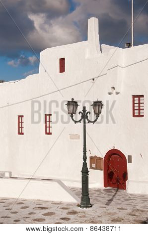 Entrance To The Famous Monastery On The Island Of Mykonos. Red Wooden Door And Street Lamp.