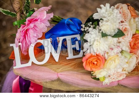 The Word Love In White Wood And Flowers