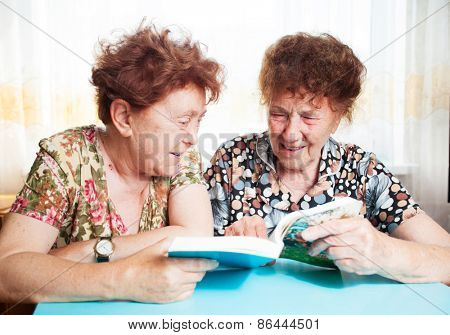 Two seniors. Old woman reading book. Friendship elderly