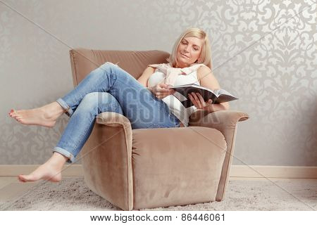 Woman reads a magazine in the armchair