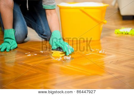 Woman cleaning the floor while kneeling at home