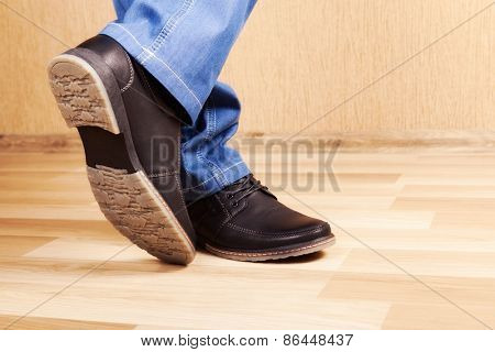 male legs in jeans and shoes in interior