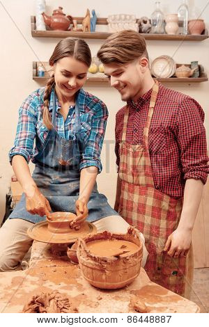 Couple works on the pottery wheel