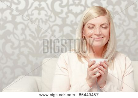 Woman drinks tea on the sofa