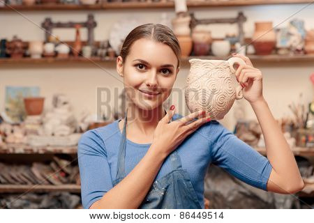 Girl holds a clay jar