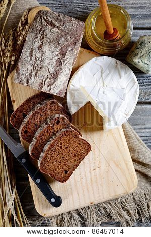 Slices Of Rye Bread, Camembert, Honey And Knife On A Board