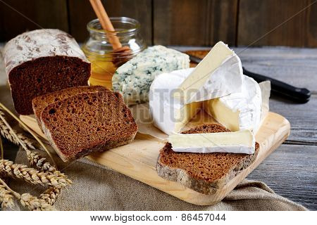Brie Cheese, Rye Bread Slices, Roquefort And Honey On A Board
