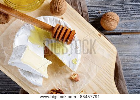 Camembert Cheese With Honey On A Wooden Board