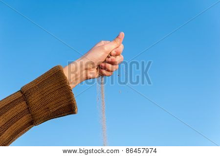 Sand Falling From The Woman's Hand