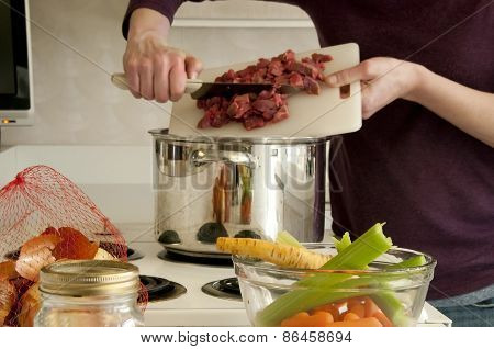 Adding Beef With Cutting Board To Soup Pot