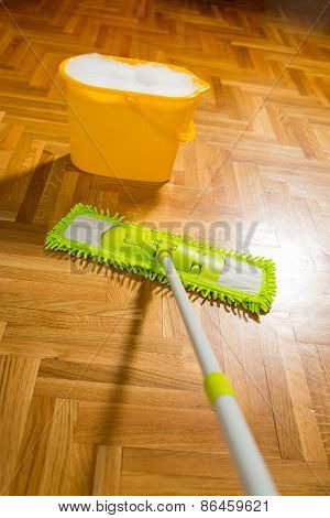 Cleaning the floor with a mop. Yellow bucket is filled with water and foam. Selective focus