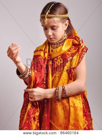 Little Girl Putting On Traditional Indian Clothing And Jeweleries
