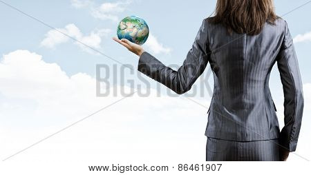 Back view of businesswoman holding earth planet in hand. Elements of this image are furnished by NASA