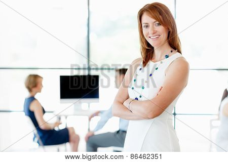 Young businesswoman standing in office with her collegue on the background