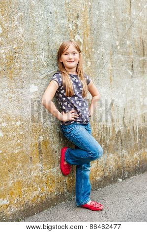 Outdoor portrait of a cute little girl wearing red moccasins