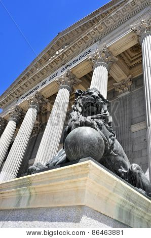 view of the main facade of the Palacio de la Cortes, seat of the Congress of Deputies in Madrid, Spain, with one of its iconic bronze lions in the foreground