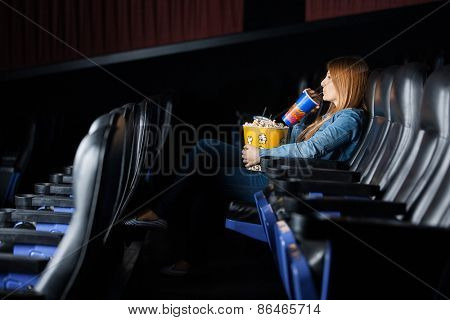 Full length side view of woman drinking cola while watching movie at cinema theater