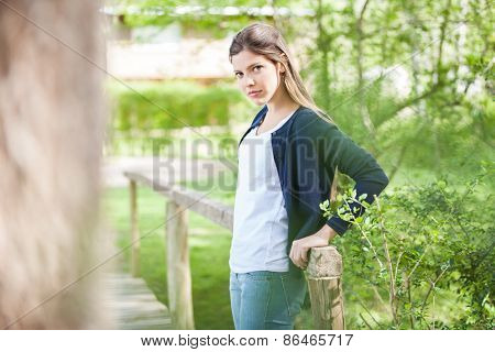 Portrait of beautiful young woman leaning on wooden bridge in park