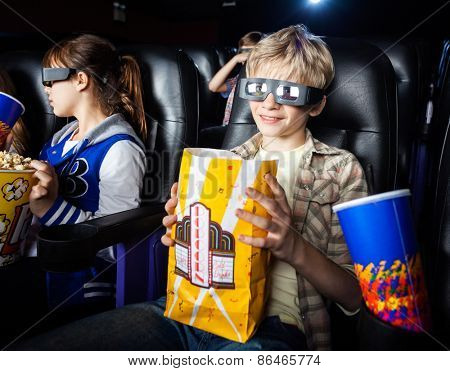 Portrait of smiling boy having snacks while watching 3D movie with sister in cinema theater