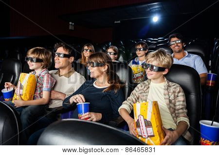 Families with snacks watching 3D movie in cinema theater