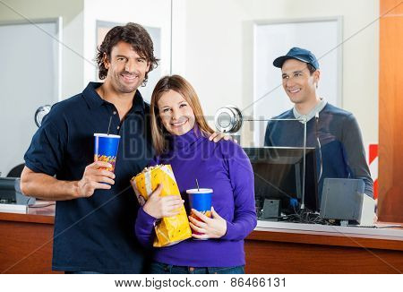 Portrait of happy mid adult couple holding snacks with male seller standing at box office counter