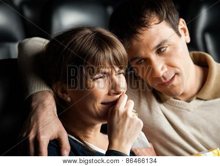 Mid adult man comforting woman crying while watching movie in cinema theater