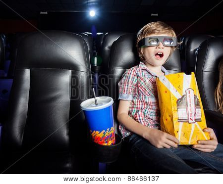 Shocked boy holding snacks while watching 3D movie in cinema theater