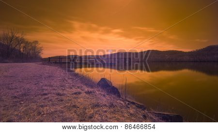 Infrared. Lock and Dam on a River with Grass and Rocks Landscape. Sunset or Sunrise.