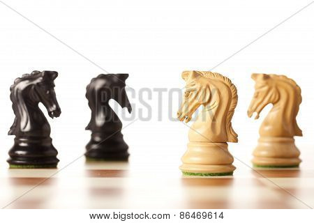 Confrontation - white and black chess knights standing next to each other on a chessboard