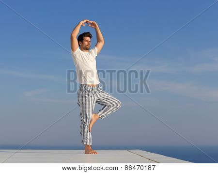 handsome young man practicing yoga on in modern home terace with ocean and sunset in background