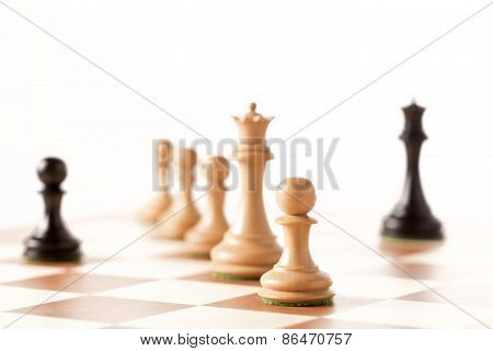 One against all - a black pawn on a chessboard with black chess pieces