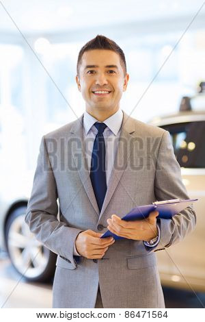auto business, car sale, consumerism and people concept - happy man with clipboard at auto show or salon