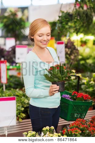 people, gardening, shopping, sale and consumerism concept - happy woman with basket choosing and buying flowers in greenhouse