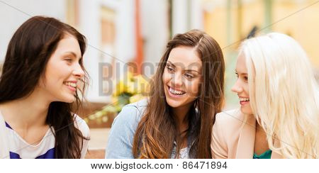 holidays and tourism concept - beautiful girls talking in cafe
