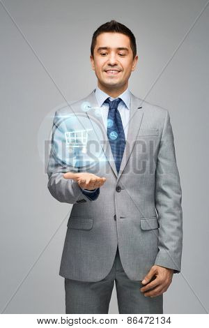 business, people, sale and technology concept - happy businessman in suit showing or holding shopping trolley hologram on hand palm over gray background